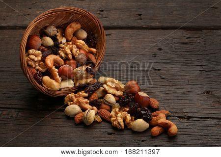 Mix of delicious nuts in a bowl over a wooden background