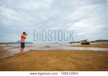 Amateur photographer takes a picture of the old Thai boat during low tide at sunset.