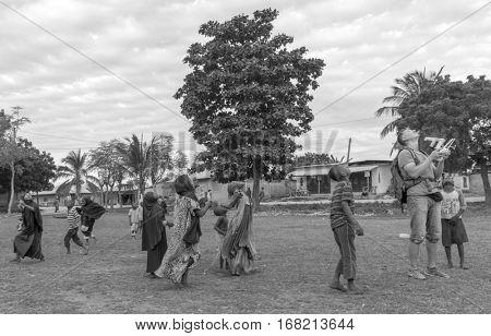ZANZIBAR, TANZANIYA- JULY 16: european man launching quadrocopter among african childrenon July 16, 2016 in Zanzibar. black and white photo