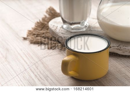 Glass pitcher cup of kefir and napkin on a white table horizontal