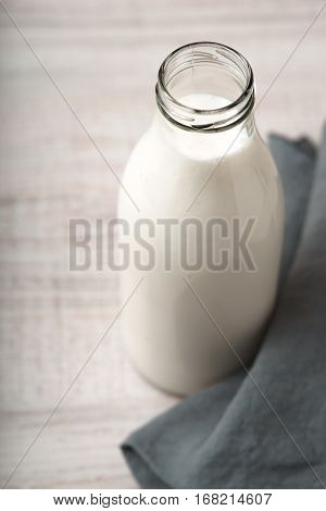 Kefir in a glass bottle on the wooden table vertical