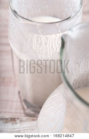 Glass of kefir and a jug on the wooden table vertical