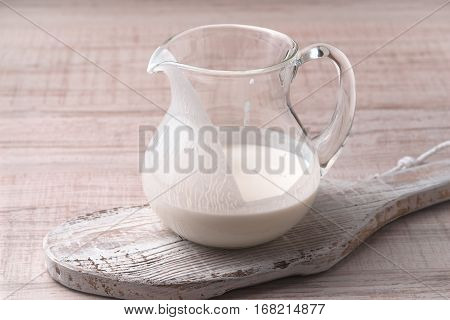Jug with kefir on a stand on a wooden table horizontal