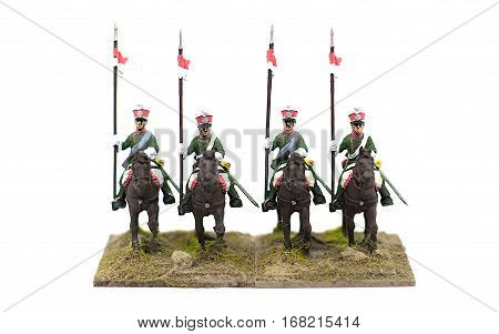 Four French cavalry toy solders riding with lancers against a white background