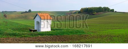 Beautiful landscape with a chapel on the green fields in south moravia czech republic waves hills with green grass.