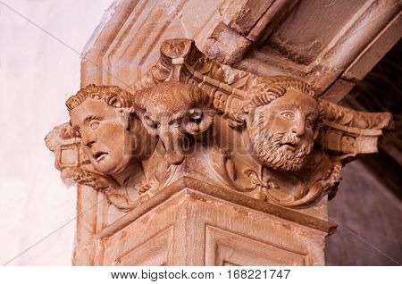 Sculptures of human heads and goat in a column