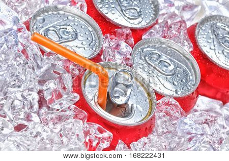 Soda Cans in Ice with a drinking straw with condensation.