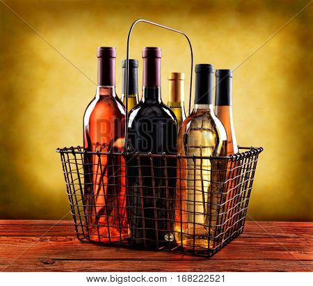 A wire shopping basket filled with wine bottles on a rustic wood table with a mottled background with warm tones.