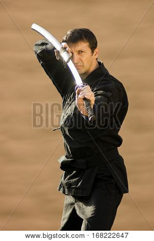 Ninja in black kimono with sword on beige background.