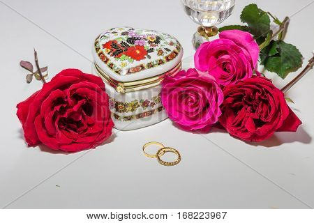 Romantic heart shaped embroidered jewelry box with bright red and pink roses with gold engagement rings for Valentines day content.