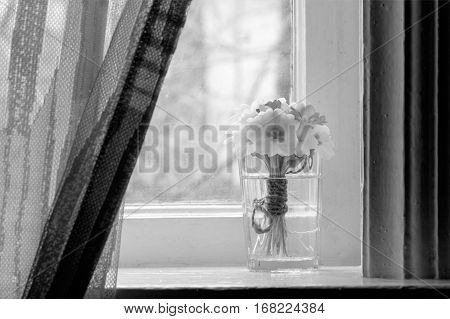 black and white photo still life a bouquet of primroses on the windowsill in a village house