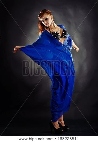 Beautiful young woman holding a blue silk dress in a fashion portrait