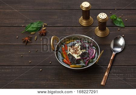 Vegan and vegetarian dish, spicy rice with red cabbage, sesame and other vegetables in bowl. Indian cuisine with herbs, healthy meal on wood background. Eastern local restaurant food.