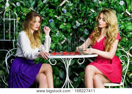 Two blonde girls chatting and having fun in a cafe. Holding a phone and having a conversation. Spring summer colorful green background. Studio shot