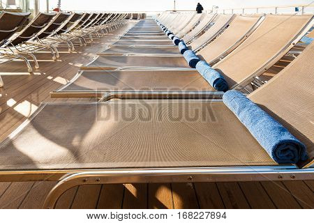 empty chairs in outdoor lounge area on stern of cruise liner