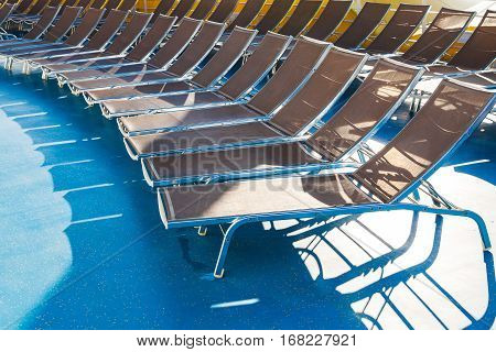 empty chairs in sunbathing area on stern of cruise liner