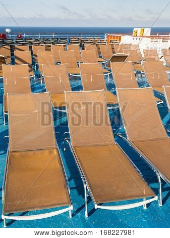 many empty sunbathing chairs on deck of cruise liner