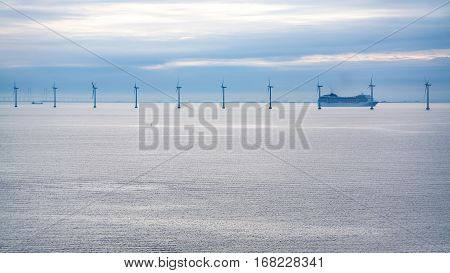 Travel to Denmark - cruise liner near offshore wind farm Middelgrunden in Oresund near Copenhagen city in Baltic Sea in blue autumn morning