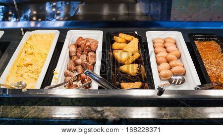 self-service buffet with meals for breakfast - bacon scrambled eggs fried sausages potato naggets boiled eggs etc