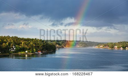 panorama of green coast of Baltic Sea with villages and rainbow over water in sunny autumn day Sweden