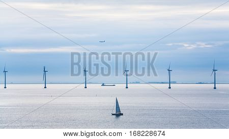 Travel to Denmark - view of yacht ship airplane and offshore wind farm Middelgrunden in Oresund near Copenhagen city in Baltic Sea in blue autumn morning