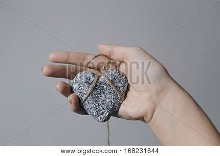 Hands holding a stone heart in jute bondage against grey background Valentine's day concept horizontal view