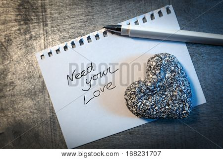 Love letter on paper with pen and stone heart on wooden rustic desk horizontal top view