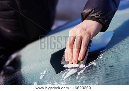 Close up of man scraping ice from the windshield of a car poster