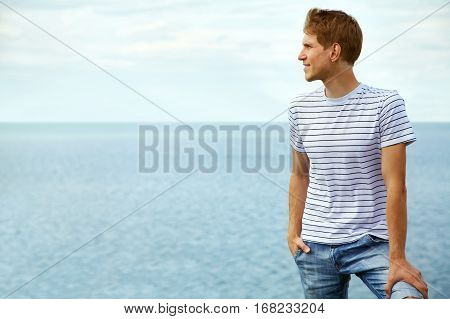 Portrait of a young smiling man on sea background. good looking man summer outdoors