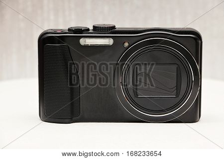Compact modern digital camera on a neutral background.