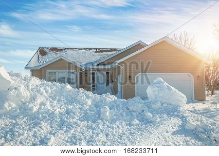 Sun setting over a house after a winter storm.