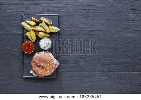Fast food restaurant dish top view with copy space. Meat cheese burger, potato chips and wedges. Take away set on dark black slate plate on wood background. Hamburger and spicy tomato sauce.