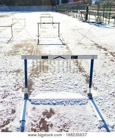 Empty running track with hurdles covered with snow