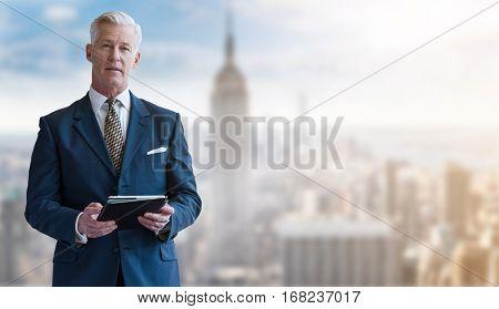 Portrait of smiling senior businessman with tablet
