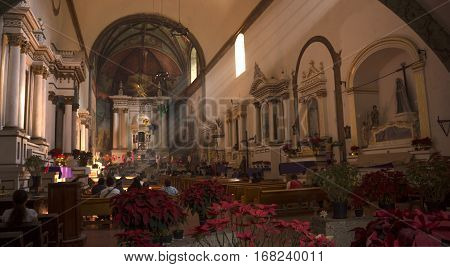 Tepoztlan Mexico - December 25 2016: Parishioners praying in the