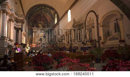 Tepoztlan Mexico - December 25 2016: Parishioners praying in the
