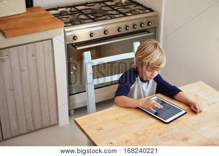 Young boy using tablet computer in kitchen, elevated view