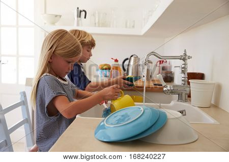 Brother and sister kneeling on chairs to wash up in kitchen