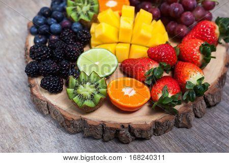 Raw fruit and berries platter mango kiwis strawberries blueberries blackberries red currants grapes selective focus