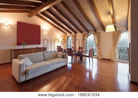 Comfortable, loft, living room with a divan and dining table, wooden floor