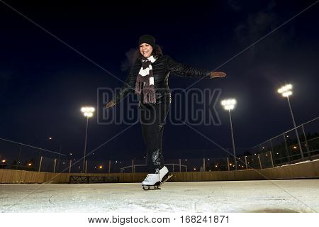 Girl skates at the rink in the winter with flood lights