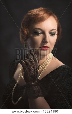 Young woman wearing black lace gloves and pearl necklace
