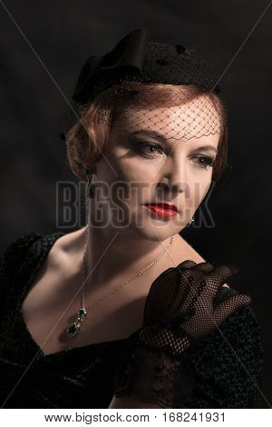 Twenties style portrait of glamorous woman wearing a pillar box hat and black lace gloves