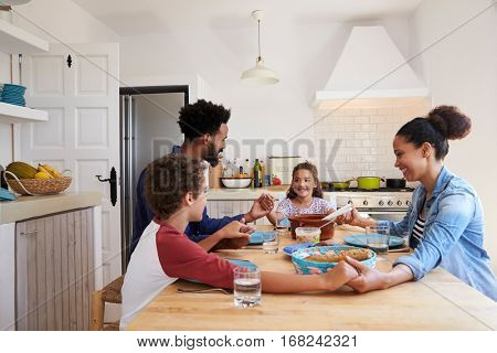 Family hold hands around the kitchen table before their meal