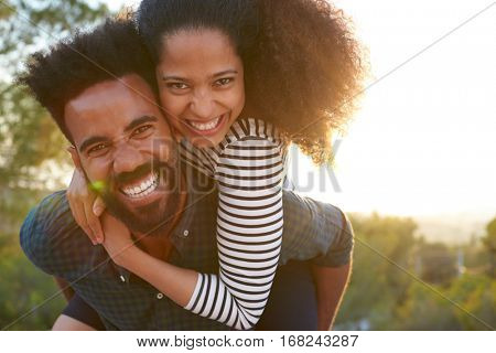 Man carrying young woman on his shoulders, looking to camera