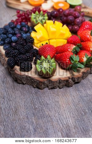 Raw fruit and berries platter mango kiwis strawberries blueberries blackberries red currants grapes, selective focus, copy space for text