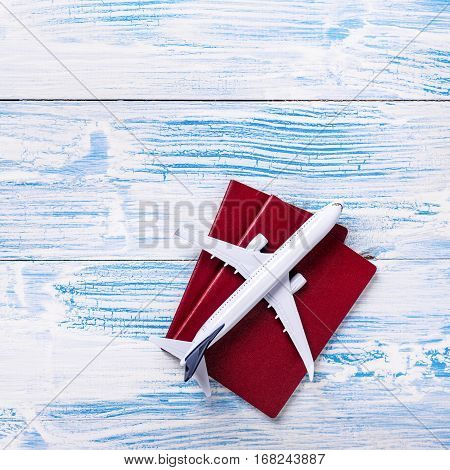 White Blank Model Of Passenger Plane And Passports On Rustic Wooden Background