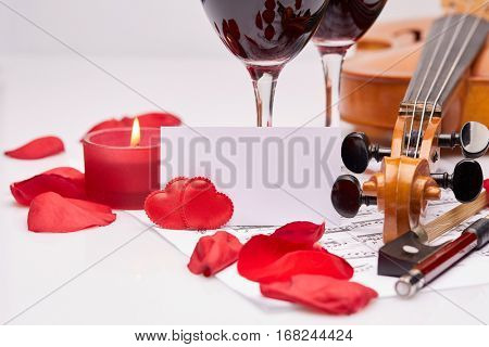 Violin (fiddle), notes, two glasses of red wine and petals of red rose on a white background. Empty bussiness card. Copy space for text.  Valentine's day.