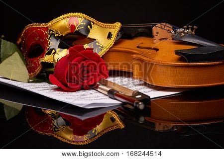 Violin (fiddle), theater mask and red rose lying on the sheet of music on a black background. String instrument.