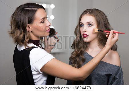 Makeup process, makeup artist using brush and compact powder and colors model at salon